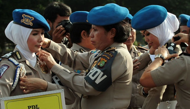 Sejumlah Polwan merapikan pakaiannya saat akan mengikuti peragaan pakaian dinas untuk Polwan berjilbab yang digelar di Lapangan Lalu Lintas Polda Metro Jaya, Jakarta (25/11). TEMPO