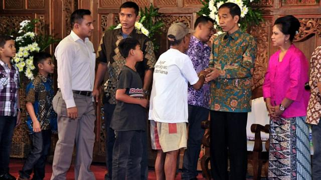 Indonesian president-elect Joko Widodo (second, right) and with his wife Iriana Widodo (right) greet hundreds of Solo city residents during an open house reception at Solo city hall in Central Java province on July 30, 2014, as part of a ceremony in celebration of the Eid al-Fitr festival. --  PHOTO: AFP