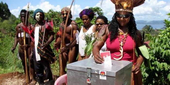Warga Papua mengenakan pakaian tradisional saat menggunakan hak suaranya dalam Pemilu Presiden 2014 di Jayapura, Rabu (9/7/2014). Pemilu memilih dua calon presiden yaitu Prabowo Subianto berpasangan dengan Hatta Rajasa dan Joko Widodo berpasangan dengan Jusuf Kalla. - KOMPAS