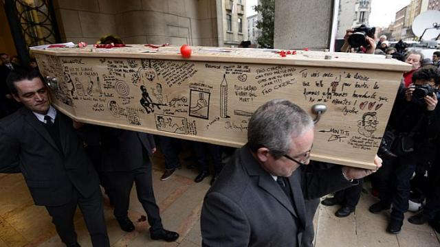 """The coffin of cartoonist Bernard """"Tignous"""" Verlhac, 57, one of the 12 people killed in the Jan 7 attack on French satirical weekly Charlie Hebdo, being carried out of the town hall of Montreuil, near Paris, during his funeral on Jan 15, 2015. -- PHOTO: AFP"""